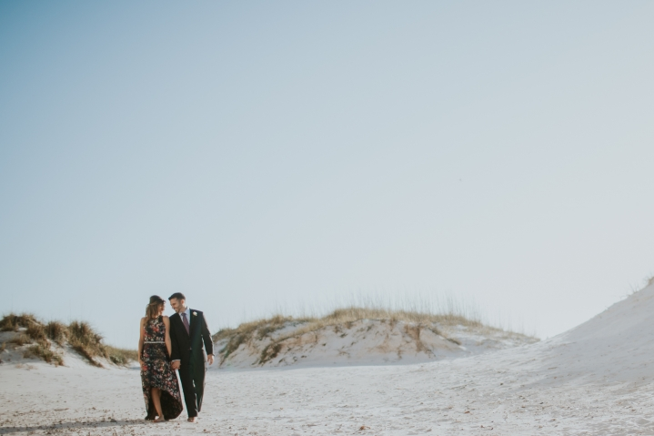 engaged couple walking on the beach